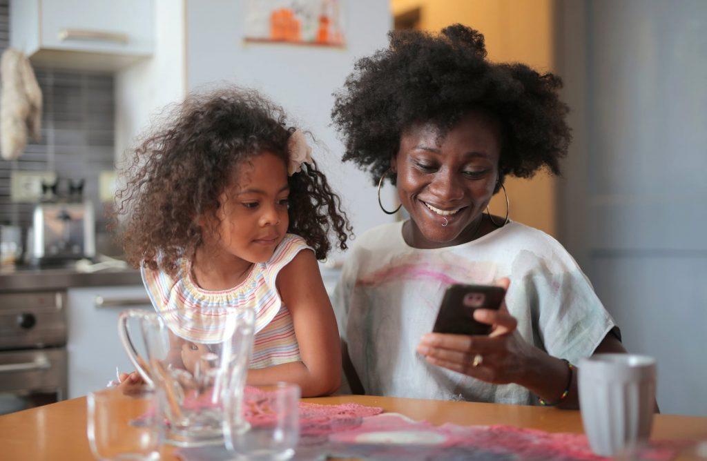 Mãe e filha olhando para um smartphone.